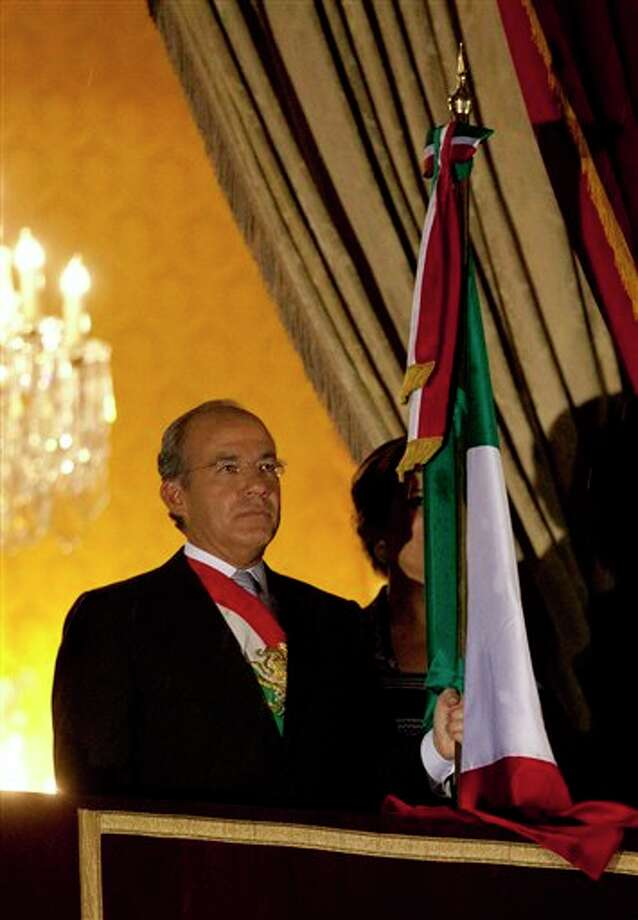 "Mexico's President Felipe Calderon attend with his nation's flag before giving the traditional ""El grito,"" or shout, to kick off Independence Day celebrations at the Zocalo in Mexico City, late Saturday, Sept. 15, 2012. Mexico is marking the 202nd anniversary of the ""Grito de Dolores,"" honoring the call to arms made by the priest Miguel Hidalgo in 1810 that began the struggle for independence from Spain, achieved in 1821. (AP Photo/Eduardo Verdugo) Photo: Associated Press"