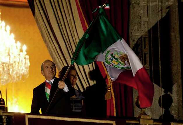 "Mexico's President Felipe Calderon waves his nation's flag after giving the traditional ""El grito,"" or shout, to kick off Independence Day celebrations at the Zocalo in Mexico City, late Saturday, Sept. 15, 2012. Mexico is marking the 202nd anniversary of the ""Grito de Dolores,"" honoring the call to arms made by the priest Miguel Hidalgo in 1810 that began the struggle for independence from Spain, achieved in 1821. (AP Photo/Eduardo Verdugo) Photo: Associated Press"