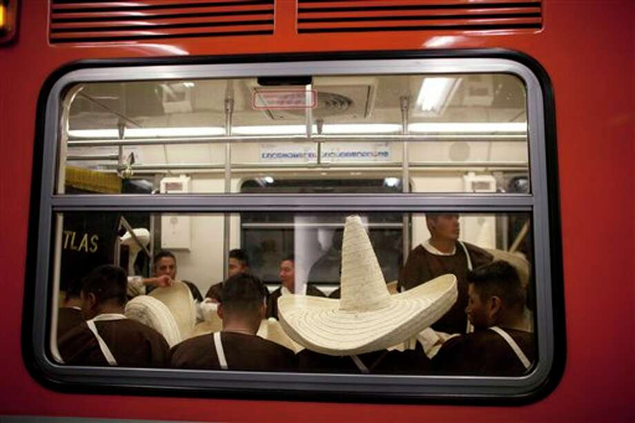 Members of the military, wearing costumes representing the 1911 revolutionary forces, ride in the subway on their way to downtown Mexico City, prior to the military parade of the Independence Day celebrations, Mexico City, Sunday Sept. 16, 2012. Mexico celebrates the 202nd anniversary of its 1810 independence uprising. (AP Photo/Alexandre Meneghini) Photo: Associated Press