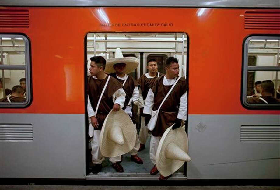 Members of the military, wearing costumes representing the 1911 revolutionary forces, stnad inside a subway train on their way to downtown Mexico City, prior to the military parade of the Independence Day celebrations, Mexico City, Sunday Sept. 16, 2012. Mexico celebrates the 202nd anniversary of its 1810 independence uprising. (AP Photo/Alexandre Meneghini) Photo: Associated Press