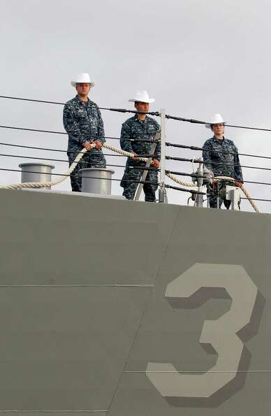Navy men and women wear cowboy hats as they prepare to throw line to the lineman on deck.