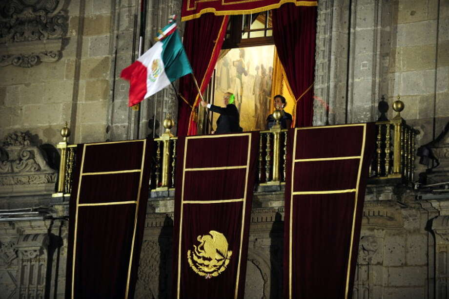 Mexican President Felipe Calderon waves the Mexican national flag beside his wife Margarita Zavala  at the start of celebrations for Mexico's Independence Day at the National Palace in Mexico City on September 15, 2012. Mexicans celebrate independence from Spanish rule 16 September.    AFP PHOTO/Alfredo Estrella        (Photo credit should read ALFREDO ESTRELLA/AFP/GettyImages) Photo: Getty Images