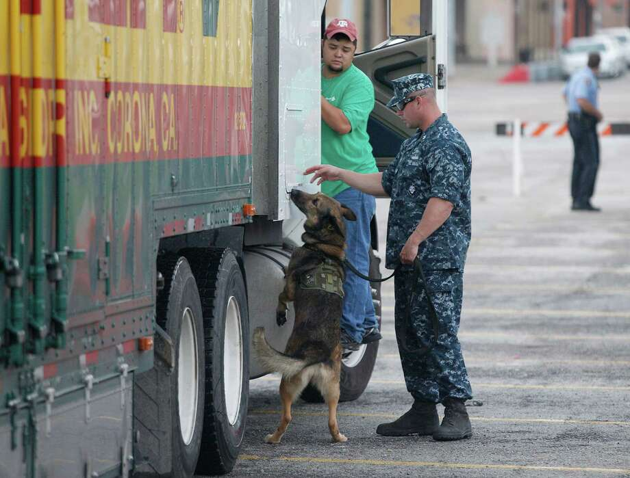 "Mayflower driver J.R Hardin watches as MA1 Nick Webster and K9  dog "" Fergina"" inspect a Mayflower truck for explosives before a transport to the USS Fort Worth in Galveston. Photo: Thomas B. Shea, For The Chronicle / © 2012 Thomas B. Shea"
