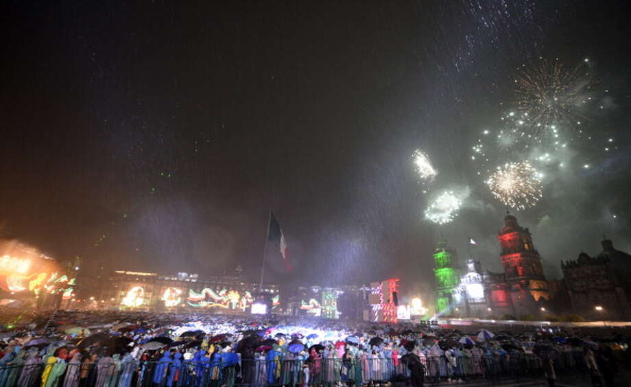 People watch as fireworks light up the sky in Zocalo Square to mark Mexico's Independence Day in Mexico City on September 15, 2012. Mexicans will celebrate independence from Spanish rule on September 16.    AFP PHOTO / Alfredo Estrella        (Photo credit should read ALFREDO ESTRELLA/AFP/GettyImages) Photo: Getty Images