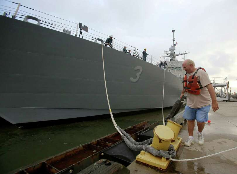 Union boatman and lineman David Walker , grabs the line  from the deck of the USS Fort Worth, as it