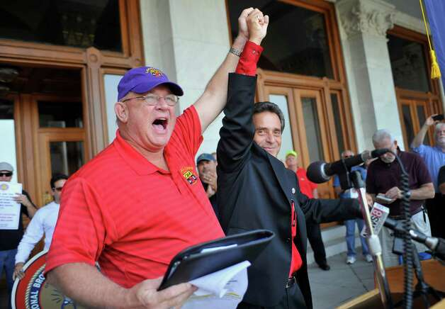 William Henderson, left, president of the Communications Workers of America Local 1298 AFL-CIO, and Frank Cirillo, of the International Brotherhood of Electrical Workers Local 420 react during a rally of Connecticut Light & Power's unionized linemen at the state Capitol in Hartford, Conn., Monday, Sept. 17, 2012. The union, which has been without a contract since June, rallied over what they say are inadequate staffing levels.  (AP Photo/Jessica Hill) Photo: Jessica Hill, Associated Press / FR125654 AP