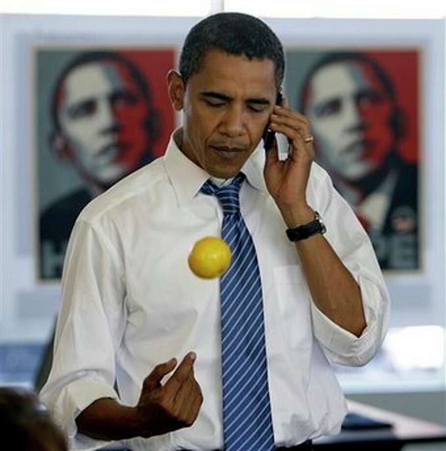 Democratic presidential candidate Sen. Barack Obama, D-Ill., makes a call to a voter, as he tosses an orange, during a stop at the Obama Kansas City campaign office in Kansas City, Mo. Saturday, Oct. 18, 2008. Photo: Alex Brandon, AP / AP