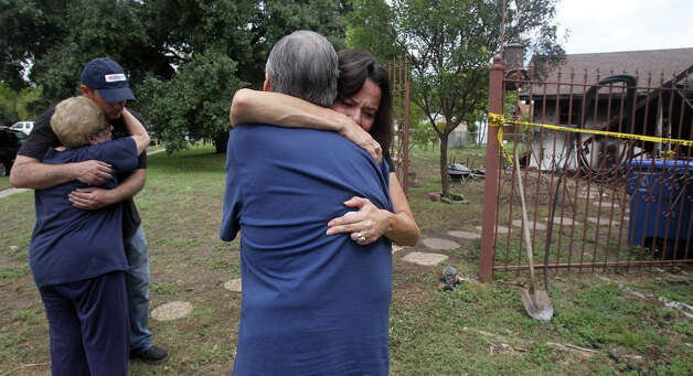 Rita Gabriel (facing, foreground) hugs family friend Joe Sepulveda (facing away) at the home of Gabriel's late father John I. Cardenas who died at his home on the 4200 block of Timberhill early Sunday September 16, 2012 after a car crashed into his house. A gas line ruptured during the crash setting the house on fire. The driver of the car also died. On the left are family friend Aniece Sepulveda and Cardenas' grandson Damien Cardenas (wearing cap). Photo: John Davenport / Express-News