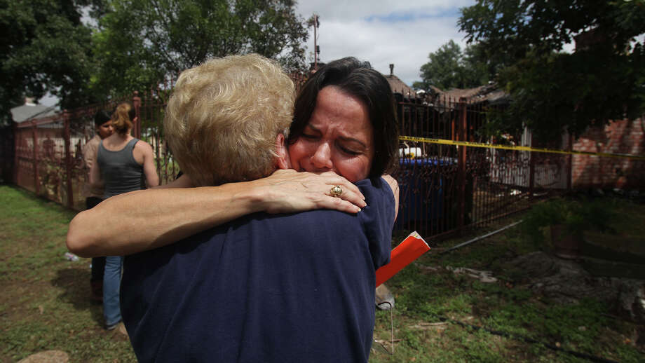 Rita Gabriel (facing) hugs family friend Aniece Sepulveda (facing away) at the home of Gabriel's late father John I. Cardenas who died at his home on the 4200 block of Timberhill early Sunday September 16, 2012 after a car crashed into the house. A gas line ruptured during the crash setting the house on fire. The driver of the car also died. Photo: John Davenport / Express-News