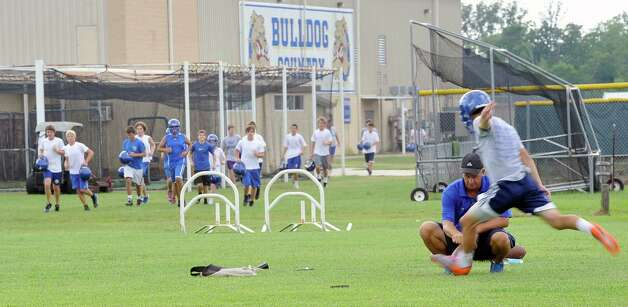 Coach Brian Arendale, right, holds the ball for kicker Andrew Cupero who had arrived ahead of the rest of the time to do some field goal kicking. The Kelly High School football team opened their practice Monday, August 6 2012 under the direction of new head coach Todd Holmes.   Dave Ryan/The Enterprise