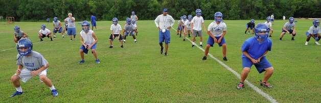 The Kelly High School football team opened their practice Monday, August 6 2012 under the direction of new head coach Todd Holmes.  As his players warmed up with exercises, he walked through the lines. Dave Ryan/The Enterprise
