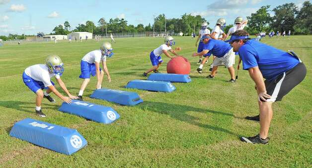Coach Jake Coulson, right, gives instructions to his players as they run over tackling pads during a drill.  Hamshire-Fannett held one of their football practices Wednesday night, August 8, 2012 and started at 6 p.m.   Dave Ryan/The Enterprise Photo: Paul Chinn