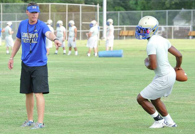 New Head Coach Kane Harris, left, gives instructions to one of his quarterbacks during the practice.  Hamshire-Fannett held one of their football practices Wednesday night, August 8, 2012 and started at 6 p.m.   Dave Ryan/The Enterprise Photo: Paul Chinn