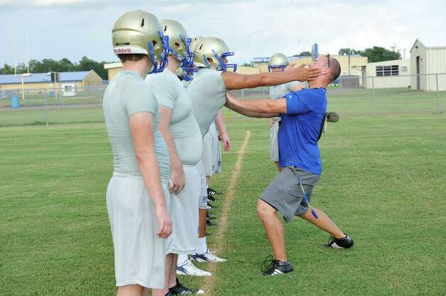 Coach Marcus Zarosky, right, gives instructions to his players as he demonstrates the stance he wants them to hold as they go through  a drill.  Hamshire-Fannett held one of their football practices Wednesday night, August 8, 2012 and started at 6 p.m.   Dave Ryan/The Enterprise Photo: Paul Chinn
