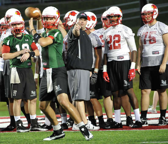 The Lamar University football team opened their practice Monday night, August 6, 2012 after the announcement that lightning was out of the area for the 2012 season.  Director of Football  Operations Chuck Langston, center, talks with some of the players.  Dave Ryan/The Enterprise