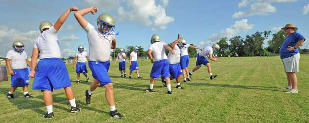 Coach Dave Westfall, right, gives instructions to his players as they run during a drill.  Hamshire-Fannett held one of their football practices Wednesday night, August 8, 2012 and started at 6 p.m.   Dave Ryan/The Enterprise
