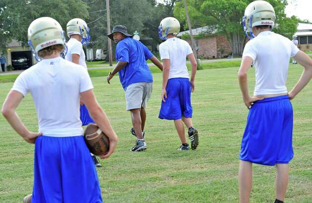Coach Prentiss Semien, middle in hat,  gives instructions to his players as they go over a passing drill.  Hamshire-Fannett held one of their football practices Wednesday night, August 8, 2012 and started at 6 p.m.   Dave Ryan/The Enterprise Photo: Paul Chinn