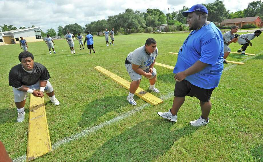 Offensive Line Coach Ed Taylor, right, yells instructions to his players during drills.  The Ozen High School football team opened practice on Monday, August 13, 2012.    Dave Ryan/The Enterprise Photo: Paul Chinn