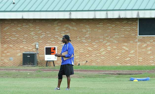 Head Coach Jeff Nelson takes a moment away from practice to check any messages on his phone. The Ozen High School football team opened practice on Monday, August 13, 2012.   Dave Ryan/The Enterprise Photo: Paul Chinn