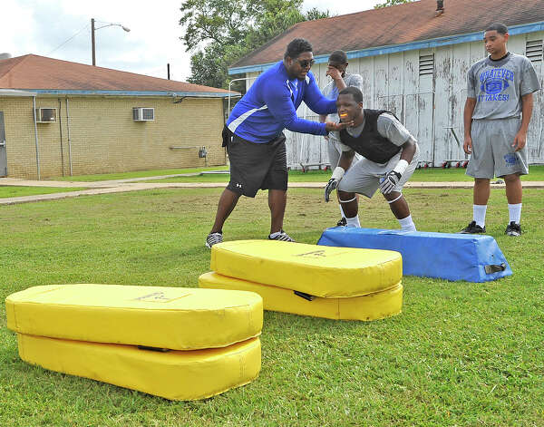 Linebackers Coach Lonnie Clayton, left, helps one of his players with his stance before starting the drill.  The Ozen High School football team opened practice on Monday, August 13, 2012.   Dave Ryan/The Enterprise Photo: Paul Chinn