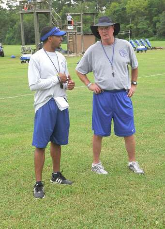 The Kelly High School football team opened their practice Monday, August 6 2012 under the direction of new head coach Todd Holmes.  As his players warmed up with exercises, he talked with quarterback coach Al Rabb, right, about the upcoming drills.   Dave Ryan/The Enterprise Photo: Paul Chinn