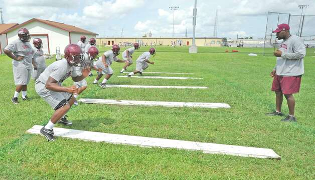 New coach Derrick Scott, right, watches some of his players run a drill during practice using straight planks.  The Central High School football team opened practice on Monday, August 1, 2012.   Dave Ryan/The Enterprise