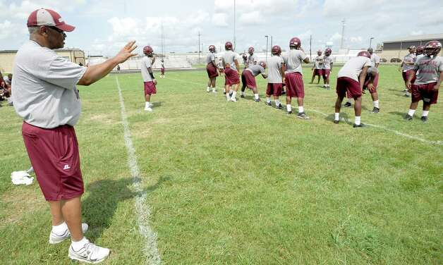 Head Coach Andrew Washington gives instructions to his offense who were running patterns against the defense. The Central High School football team opened practice on Monday, August 1, 2012.  Dave Ryan/The Enterprise Photo: Paul Chinn