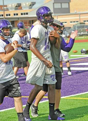 Quarterback #15, A. J. Smith, middle, hangs on to the ball as he walks through a drill with head coach Brandon Faircloth, right who was slapping at the ball, trying to knock it from his grasp.  The Port Neches-Groves High School football team had  their second practice of the morning Tuesday August 14, 2012 after spending part of the morning having  their pictures taken.  Dave Ryan/The Enterprise Photo: Paul Chinn