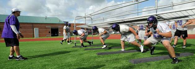 Offensive line coach Toby Latiolais, left, watches as his players come out from a cage device that forces them to stay low as they run from their starting stance over a set of wooden planks. The Port Neches-Groves High School football team had  their second practice of the morning Tuesday August 14, 2012 after spending part of the morning having  their pictures taken.  Dave Ryan/The Enterprise Photo: Paul Chinn
