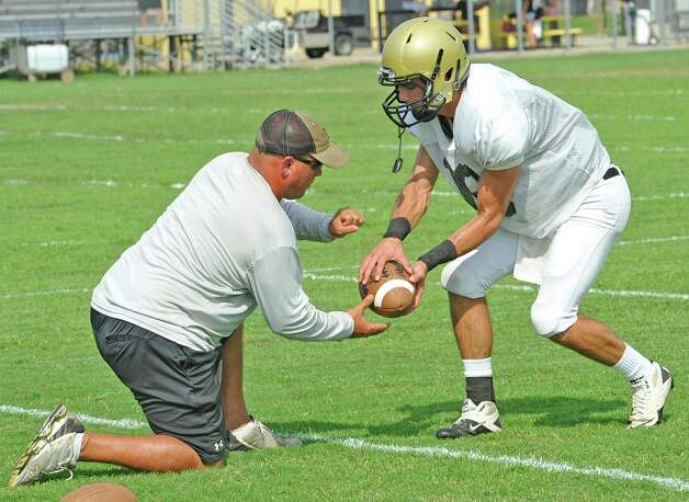 Nederland quarterback Carson Raines, right, runs through drills during practice Monday August 27, 2012 as his quarterback coach Monte Barrow, left, works with him.  Dave Ryan/The Enterprise