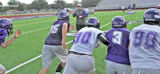 "Head coach Brandon Faircloth, center, yells ""go"" for the players to run across the field and back as fast as they can during a running drill.  The Port Neches-Groves High School football team had  their second practice of the morning Tuesday August 14, 2012 after spending part of the morning having  their pictures taken.  Dave Ryan/The Enterprise Photo: Paul Chinn"