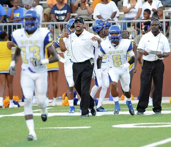 "Assistant Coach Caleb Ceasar, left, signals for adjustments to the offensive line during the game against West Brook. Ozen High School met West Brook High School in the football season opener Friday August 31, 2012 at the Carrol A ""Butch"" Thomas Educational Support Center.   Dave Ryan/The Enterprise Photo: Paul Chinn"
