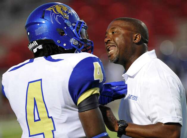 Head Coach Jeff Nelson, right, has a discussion with #4, Tony Brown, before sending him back onto the field during the game with West Brook.   Dave Ryan/The Enterprise Photo: Paul Chinn