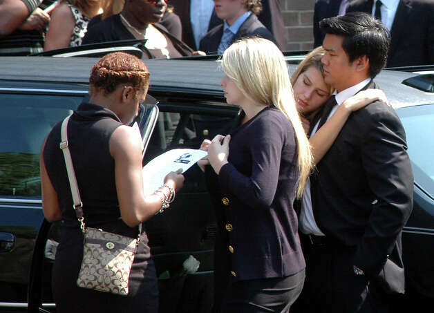 Kelley and Lauren McInerney are consoled after of the funeral service for their brother, Marcus Dixon McInerney, at the Church of the Holy Spirit in Stamford, Conn. on Monday Sept. 17, 2012. Photo: Cathy Zuraw / Stamford Advocate