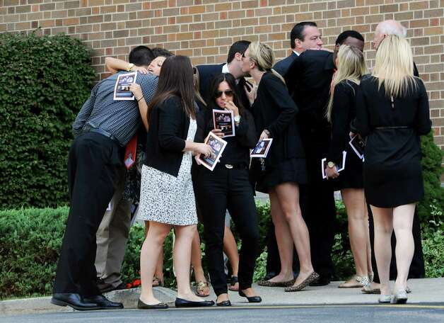 Friends console each other before they enter the Church of the Holy Spirit in Stamford, Conn. for a funeral service for Marcus Dixon McInerney on Monday Sept. 17, 2012. Photo: Cathy Zuraw / Stamford Advocate