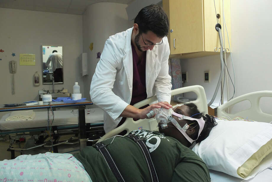 Technician Aaron Martinez fits Dajaneik Newman with a mask at the Children's Sleep Disorder  Center. Photo: Kin Man Hui, San Antonio Express-News / ©2012 San Antonio Express-News