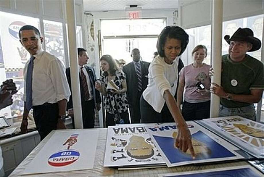 Democratic presidential hopeful, Sen. Barack Obama, D-Ill., left, and his wife Michelle look at posters at Go Tell Mama! The Officially Unofficial Obama Art Show in Raleigh, N.C.,Tuesday, May 6, 2008. Voters in both North Carolina and Indiana are crowding polling places Tuesday for the states' primary elections, the largest remaining contests in the Democratic presidential nomination struggle between Obama and Sen. Hillary Rodham Clinton. Photo: Jae C. Hong, AP / AP