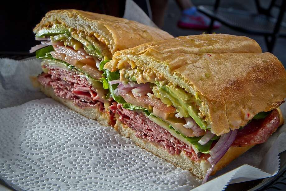 Lou's Cafe (5017 Geary Blvd, San Francisco): The Ami-cado sandwich, shown above, is one of the favorites at this Richmond District shop, according to the staff. The Ami-cado comes loaded with pastrami, salami, avocado pepper jack cheese and Lou's special sauce. Customers also go crazy for the LLB Special, Roma's Club, the chicken pesto and the Risky Bizness (a hot pastrami brisket with crab salad, bacon, avocado, pepper jack cheese, pepperoncinis and Lou's special sauce). Photo: John Storey