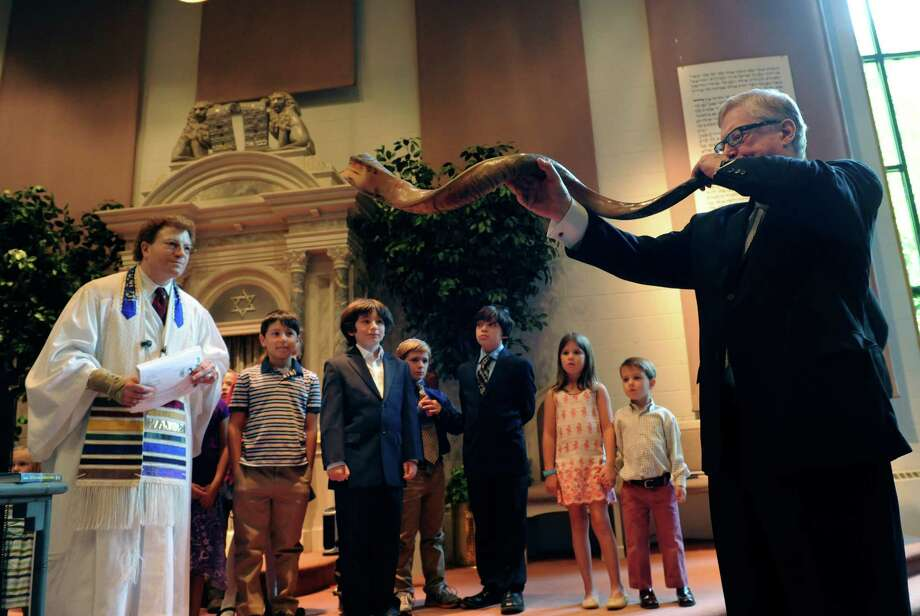 Rabbi Andy Sklarz and children listen to Brad Powell, of New Canaan, play the shofar during a Rosh Hashana family service at Greenwich Reform Synagogue Monday, Sept. 17, 2012. Rosh Hashana, the Jewish New Year, began on the evening of Sept. 16 and ends on the evening of Sept. 18. Photo: Helen Neafsey / Greenwich Time