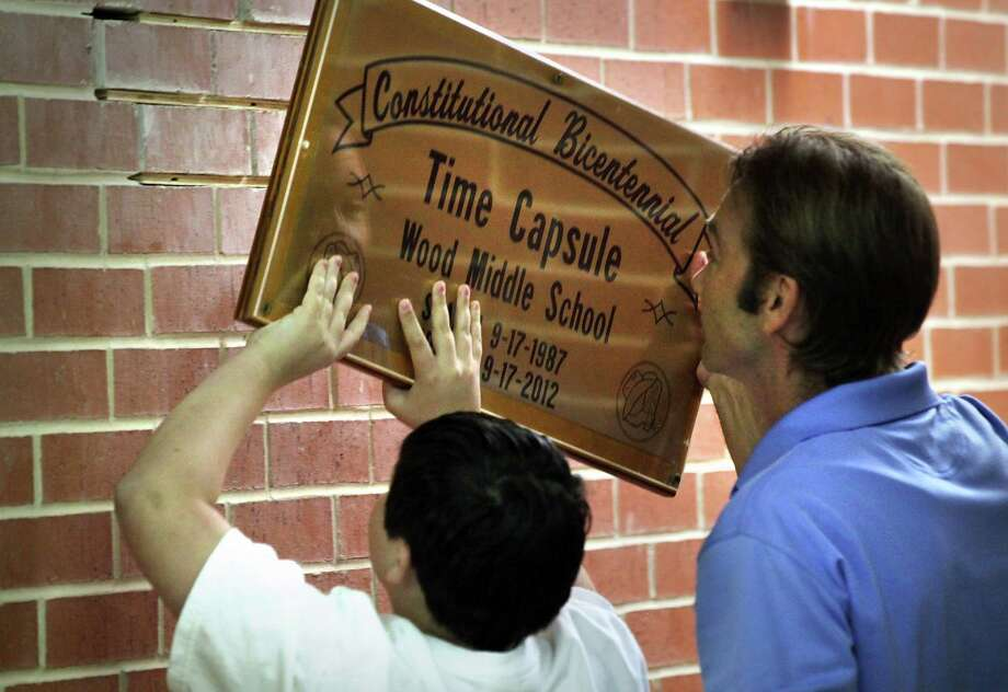 David Dunn, right, who was a student at Wood Middle School in 1987, and his son Camren Dunn, left, who is a current student at the school, remove the plaque revealing the time capsule at Wood Middle School from 25 years ago. It was opened today, Monday, Sept. 17, 2012, and will be resealed with current items selected by students and faculty members. Photo: BOB OWEN, San Antonio Express-News / © 2012 San Antonio Express-News