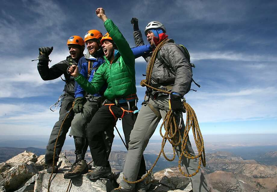"From left, Eric Gray, veteran Andrew Sullens, Timmy O'Neill and veteran Mike Kirby celebrate climbing Grand Teton, Sept. 11, 2012. 'This is an accomplishment. If I can do this, I can do so much more,"" said Sullens, placing two rocks in his pocket. (AP Photo/The Salt Lake Tribune, Leah Hogsten) Photo: Leah Hogsten, Associated Press"
