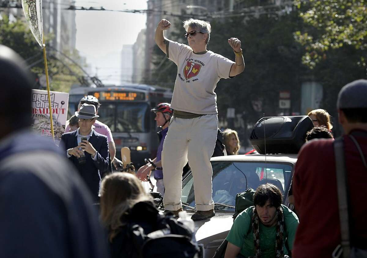 A woman danced on top of a car parked in the middle of a blocked Market Street. To mark the one year anniversary of the Occupy Wall Street movement, local occupy groups and their supporters staged a number of protests in San Francisco, Calif. Monday September 17, 2012.