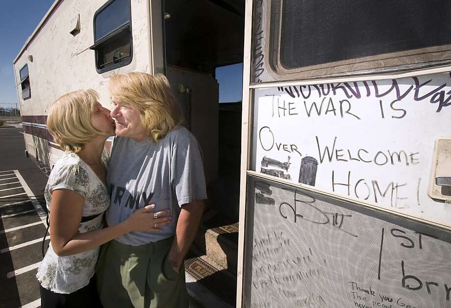George Jones of Biloxi, Miss., gets a quick kiss from his wife Jennifer sit at their motor home door while in Victorville, Calif., Monday Sept. 17, 2012. The two have been traveling the country seeking people to sign messages to soldiers and donate to www.woundedwarriorproject.org. (AP Photo/The Victor Valley Daily Press, James Quigg) Photo: James Quigg, Associated Press