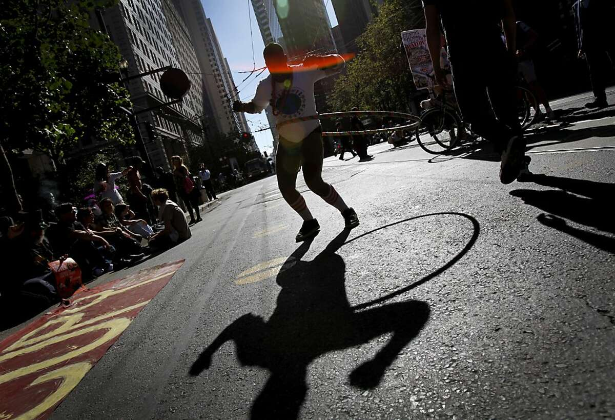 A girl who goes only by Lullaby hula-hoops in the middle of Market St. as Occupy protestors shut down traffic to celebrate the one-year anniversary of the Occupy movement in San Francisco, Calif., Monday, September 17, 2012.