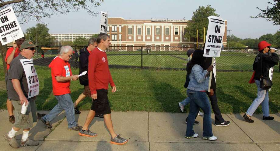 Smaller, more subdued groups of teachers picket outside Morgan Park High School in Chicago, Monday, Sept. 17, 2012, as a strike by Chicago Teachers Union members heads into its second week. Mayor Rahm Emanuel said he will seek a court order to force the city's teachers back into the classroom. (AP Photo/M. Spencer Green) Photo: M. Spencer Green
