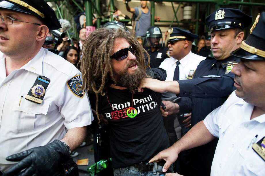 A.J. Redkey is arrested during an Occupy Wall Street march, Monday, Sept. 17, 2012, in New York. A handful of Occupy Wall Street protestors have been arrested during a march toward the New York Stock Exchange on the anniversary of the grass-roots movement. (AP Photo/John Minchillo) Photo: John Minchillo