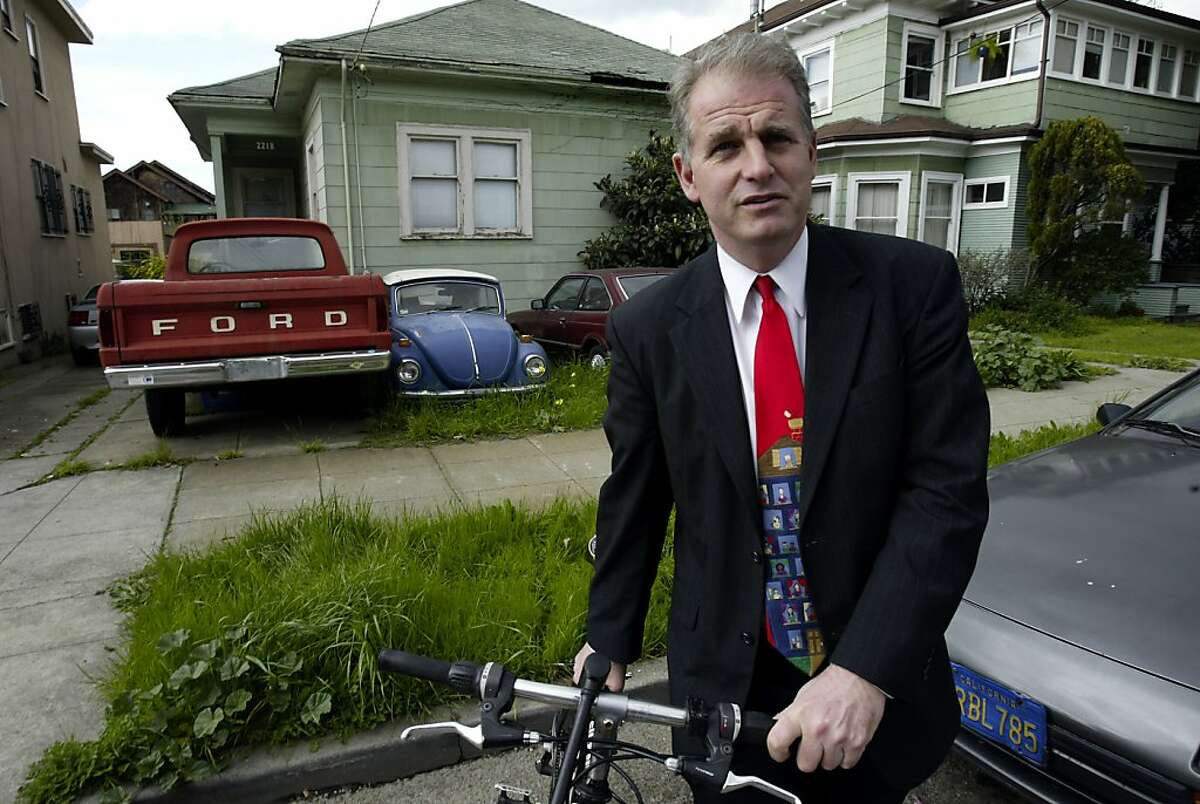 Berkeley councilman Kriss Worthington stands with his his bike on Grant Street, next to a house that has cars in the front yard. A new car tax is being proposed in Berkeley for residents who own multiple cars. Event on 2/20/04 in Berkeley. Darryl Bush / The Chronicle