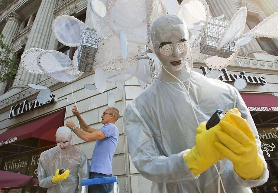 "Steven Vizena, of Hoboken, N.J., works on his ArtPrize entry ""Cloud Zombies connected or disconnected"" outside Kilwins Chocolates & Ice Cream in Grand Rapids, Mich., Monday, Sept. 17, 2012. Vizena said the work is his observation of people detached from the world on their mobile devices. (AP Photo/The Grand Rapids Press, Cory Morse) Photo: Cory Morse, Associated Press"