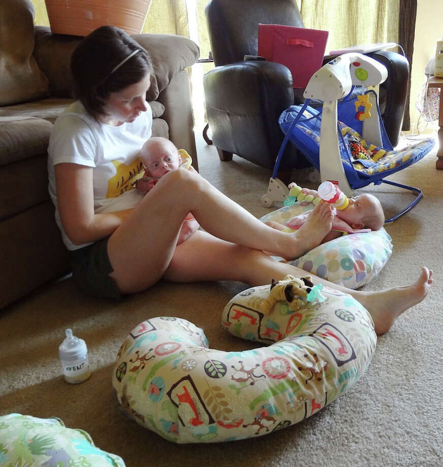 Lauren Perkins feeds Levi on her lap while balancing a bottle with her foot for Caroline.