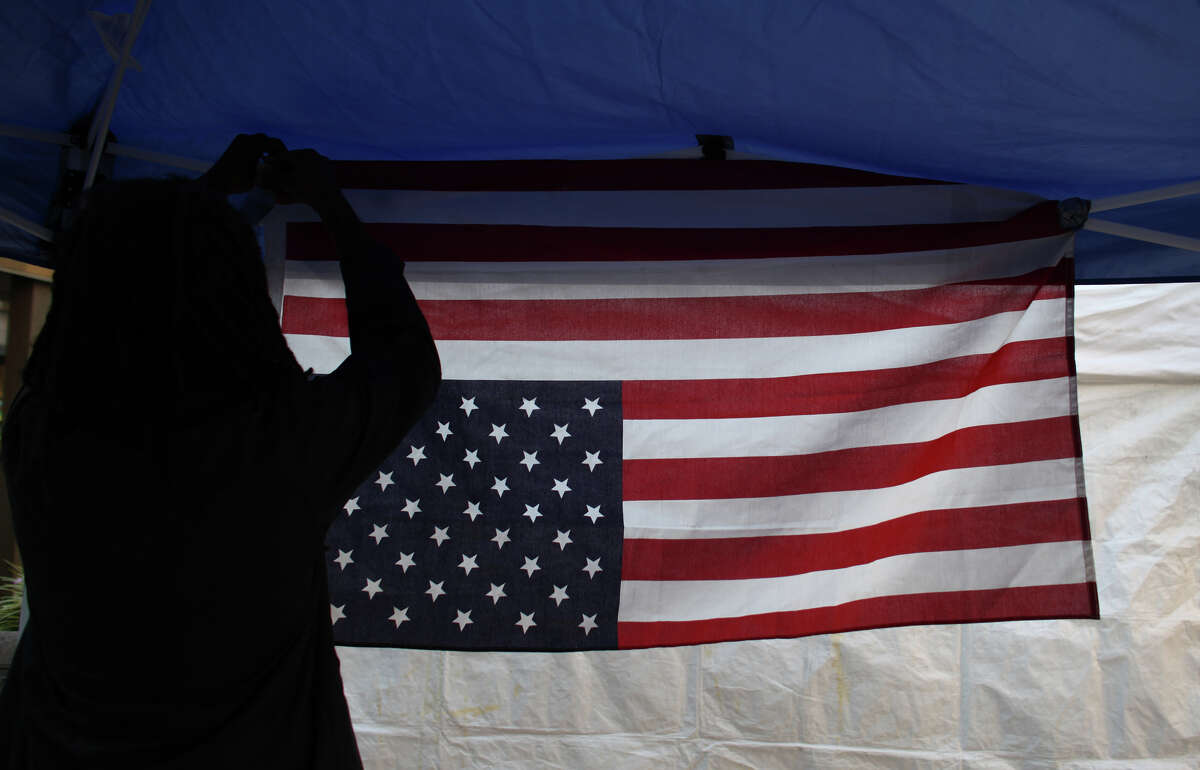 An occupier hangs a flag during the first anniversary of the Occupy movement at Westlake Park.